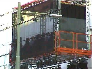 Het publiek kijkt van buiten naar de stukken die binnen worden opgevoerd ...